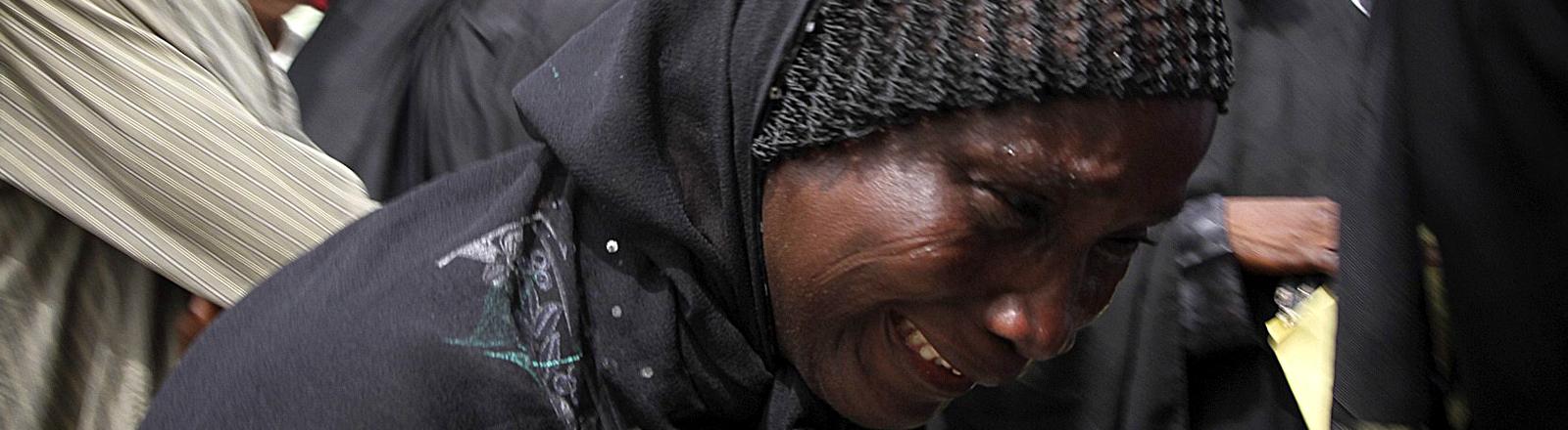 Eine Frau mit schwarzem Schleier weint um die in Nigeria von Boko Haram entführten Mädchen.