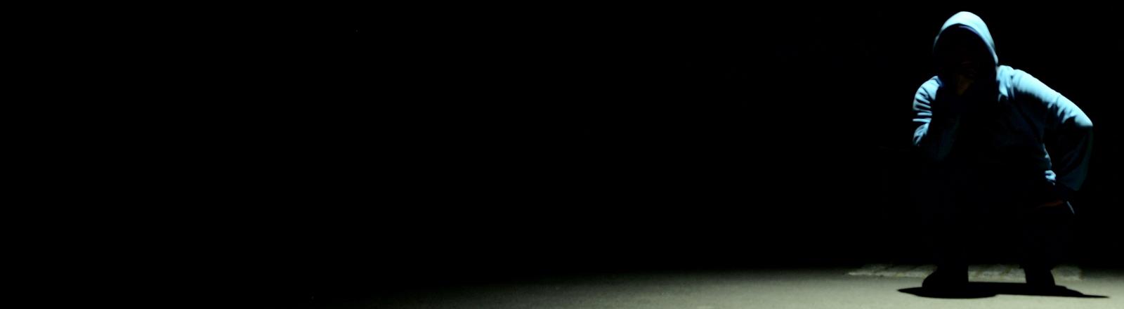 Ein Mann mit Kapuzenpulli hock im Schatten. Sehr mysteriös!