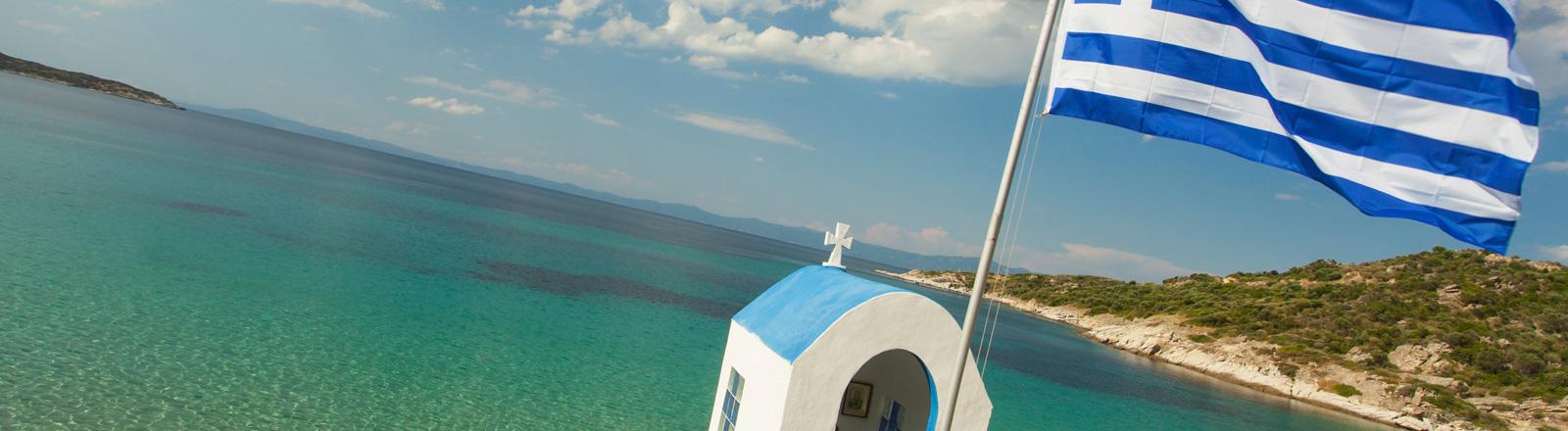 Blick auf das Meer in Griechenland. Rechts flatter die griechische Nationalflagge. In der Mitte ist das Dach einer kleinen Kapelle zu sehen.