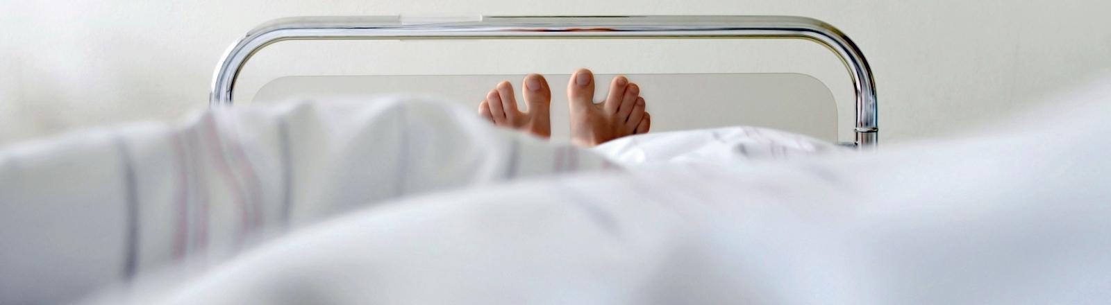 Unter der Decke eines Krankenhausbettes schauen zwei Füße hervor.
