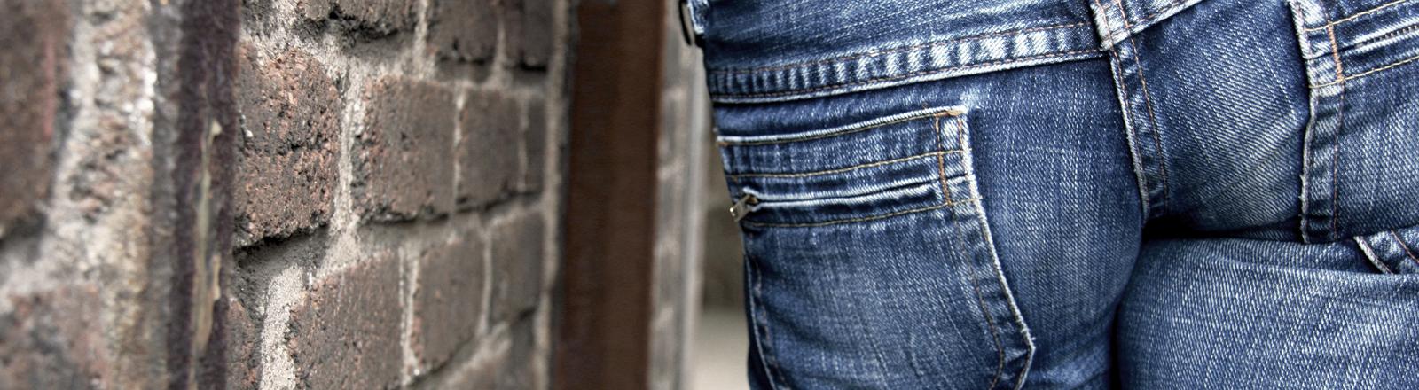 Ein Po in Jeans verpackt lehnt an einer Mauer.