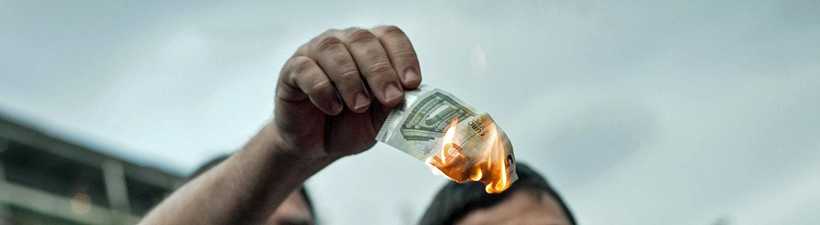 Zwei Euro-Gegner verbrennen 5€-Scheine in Athen