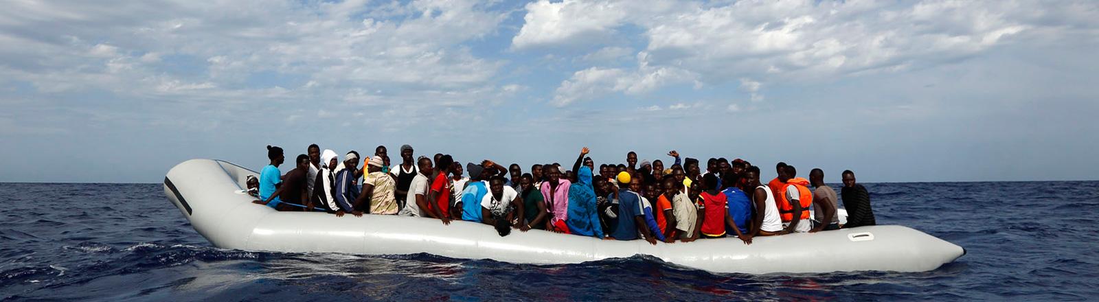 Etwa 100 Flüchtlinge sitzen in einem Schlauchboot vor der italienische Insel Lampedusa; Bild: dpa