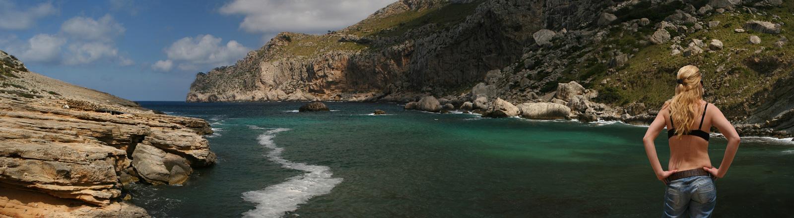 An einer Bucht steht eine Frau und blickt Richtung Meer. Sie trägt Jeans und einen BH.
