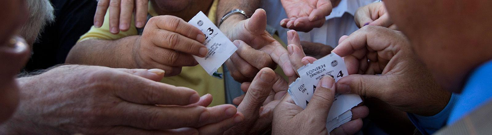 Vor einer Bank in Athen drängen sich Rentner, um eine Nummer für die Position in der Warteschlange zu ziehen.