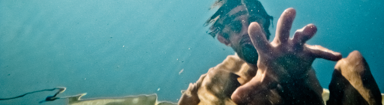 Ein Mann streckt seine Hand aus, um jemanden aus dem Wasser zu ziehen.