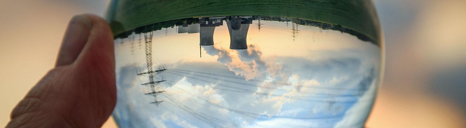 Hand hält Kugel mit Atomkraftwerk - auf den Kopf gestellt