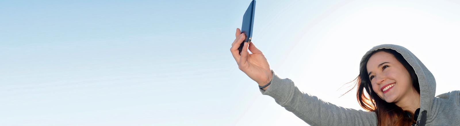 Eine Frau reckt ihr Handy in die Luft.