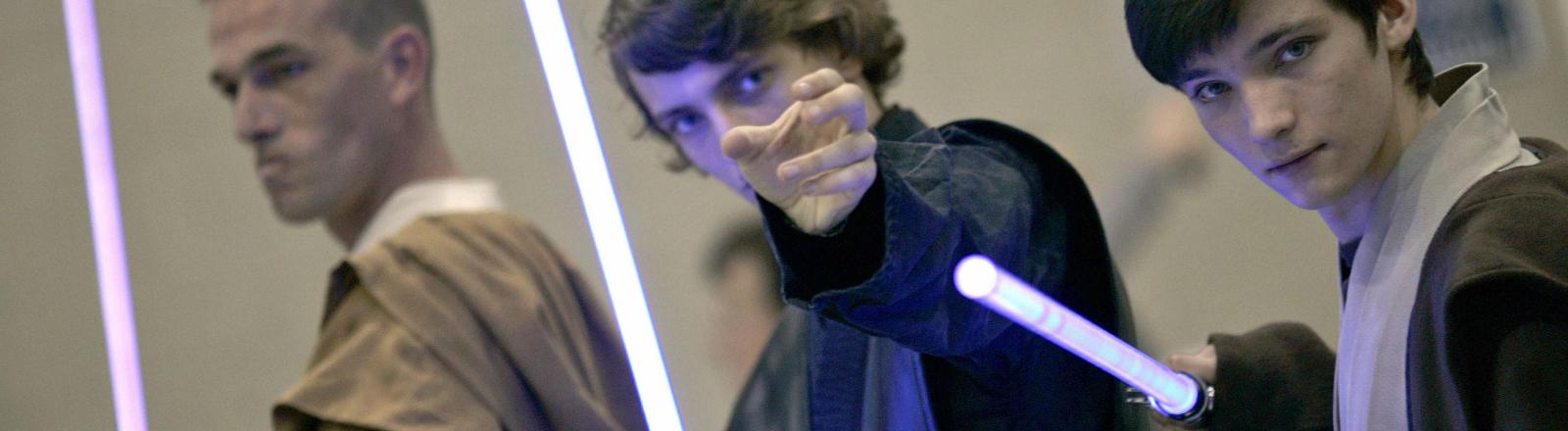 Drei Jedis posieren für die Kamera mit ihren Lichtschwertern.