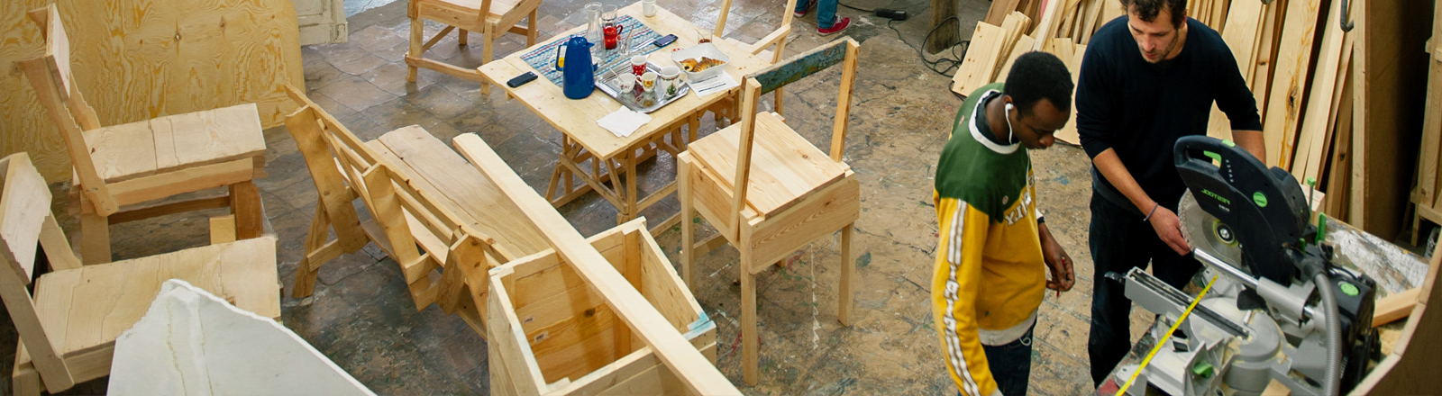 Zwei Männer arbeiten in einer Werkstatt.