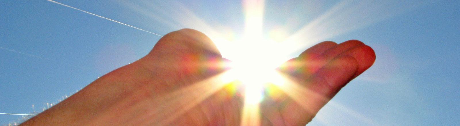 Eine Hand, so geformt, dass sie die strahlende Sonne wie eine Schalte hält