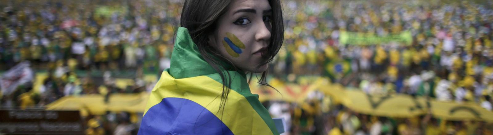 Hunderttausende demonstrieren in Brasilia in Brasilien. Im Vordergrund steht eine junge Frau, die in die Kamera blickt. Sie hat die Nationalflagge um ihre Schultern gelegt; Bild: dpa