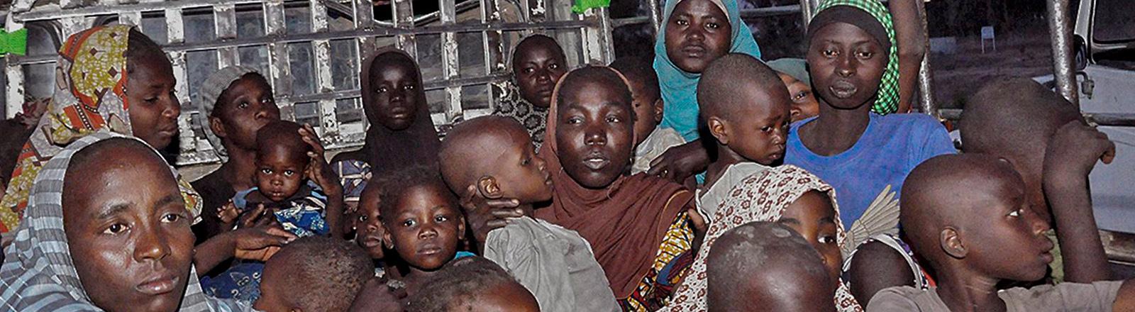 Auf einem offenen Jeep sitzen Frauen mit Kindern. Sie wurden im Mai 2015 aus den Händen von Boko Haram befreit; Foto: dpa