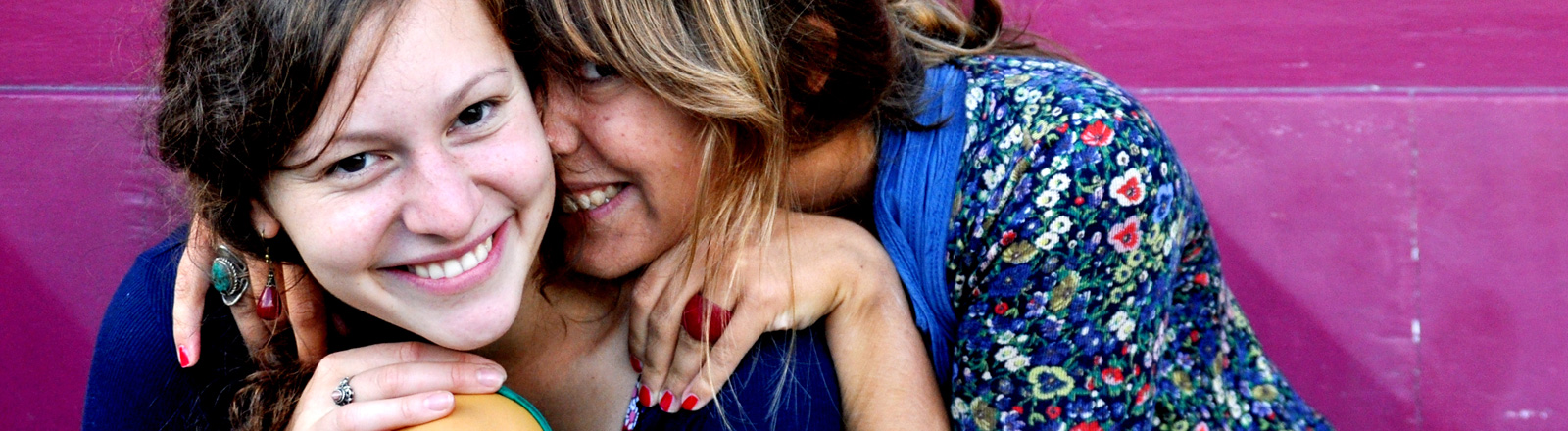 Zwei Frauen sitzen eng zusammen und lachen. Die eine hat den Arm über die Schulter der anderen gelegt.