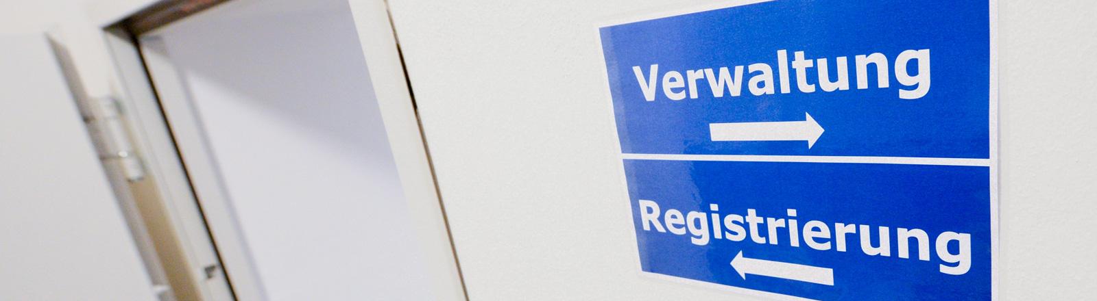 An einer weißen Wand hängt ein blaues Schild auf dem stehen die Worte Verwaltung und Registrierung. Pfeile darunter weisen nach links beziehungsweise nach rechts; Bild: dpa