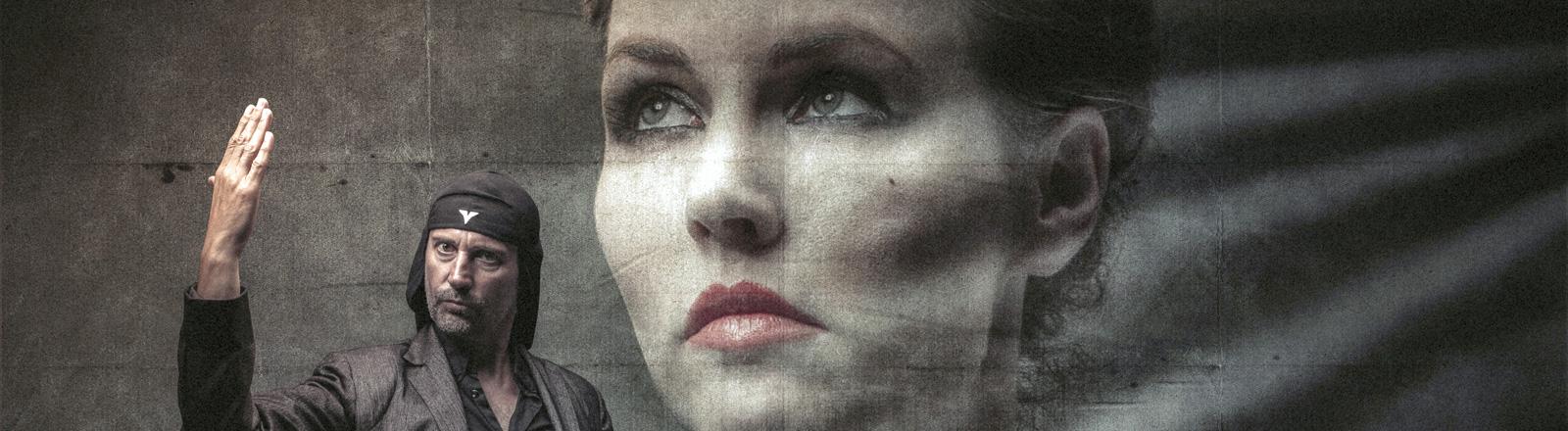 Die Band Laibach. Milan Fras steht vor einem großen Plakat, das das Gesicht von Mina Spiler zeigt; Bild: Luka Kase | Laibach | dpa