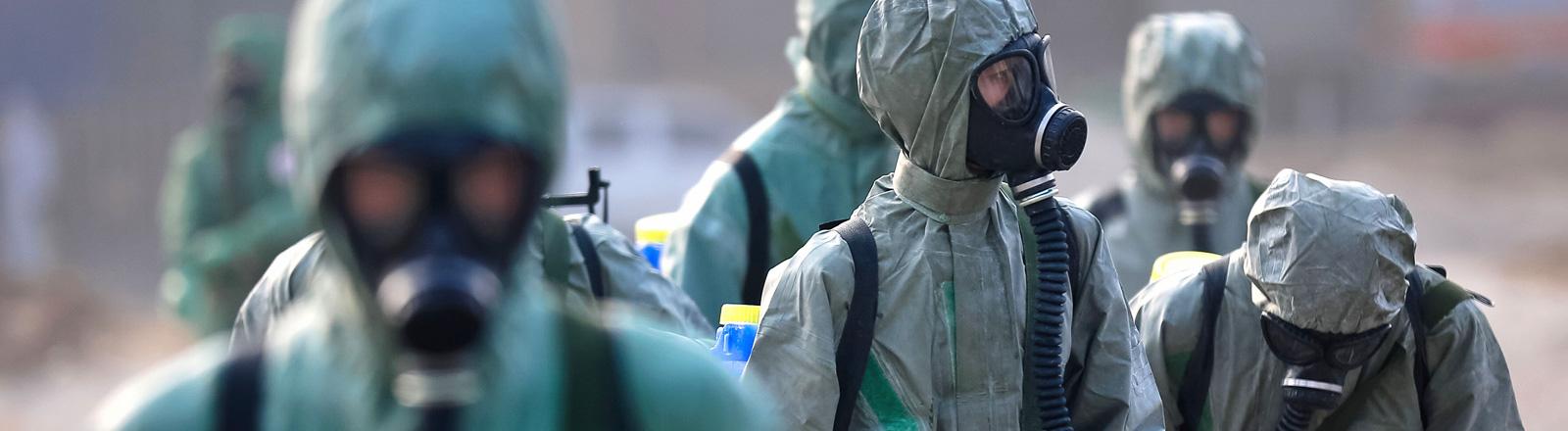 Nach Explosionen in einem Gefahrgutlager in der chinesischen Hafenstadt Tianjin desinfizieren Rettungskräfte in Schutzanzügen die Gegend; Bild: dpa