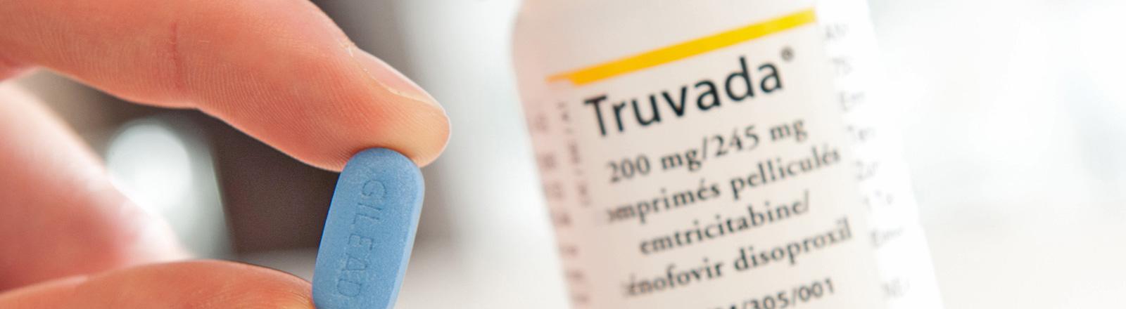 Eine Hand hält eine blaue Pille, das Anti-Aidsmittel Truvada. Daneben steht eine weiße Dose auf der Truvada steht; Bild: dpa