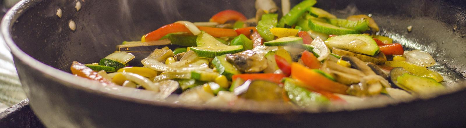 In einer Pfanne brutzelt Gemüse.