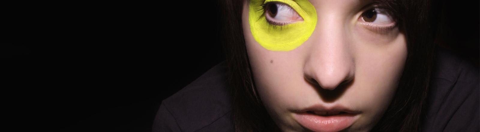 Eine Frau mit gelb ummalten Auge schaut etwas erschrocken.