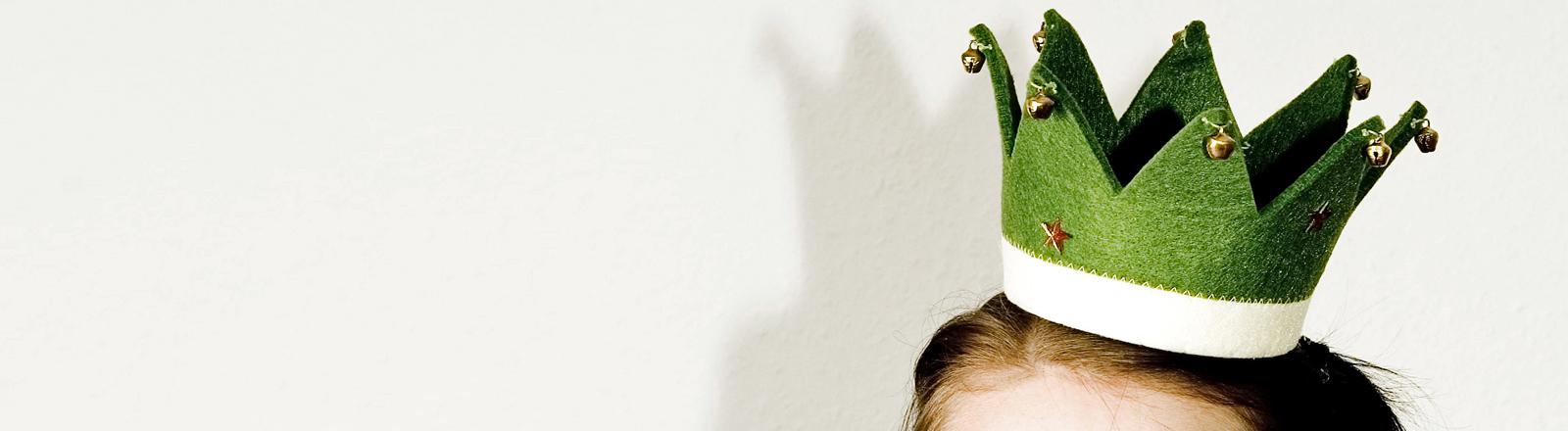 Eine Frau trägst eine nicht so schön aussehende Krone aus Filz.