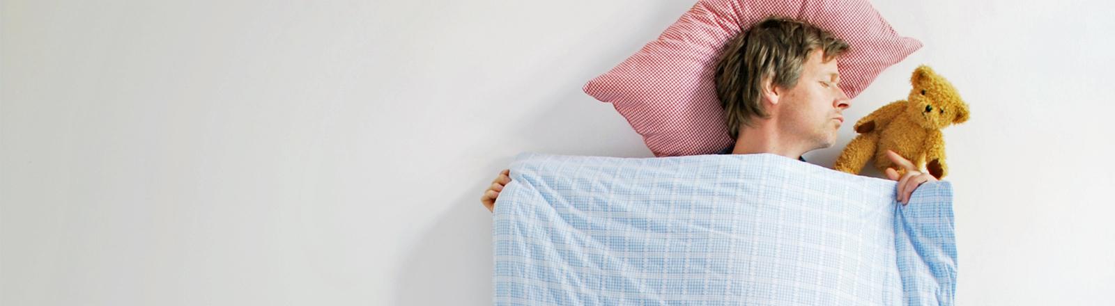 Ein Mann liegt im Bett und kuschelt mit einem Teddy.