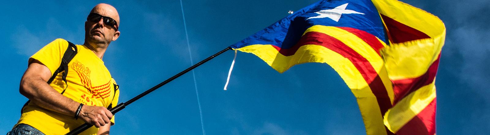 Ein Demonstrant in Spanien schwingt die katalonische Flagge.