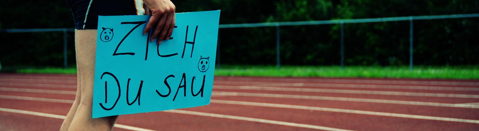 """Ein Mann steht an einer Tartan-Rennbahn und hält ein Schild in der Hand mit der Aufschrift: """"Zieh, du Sau"""" (lama-photography / photocase.de)."""