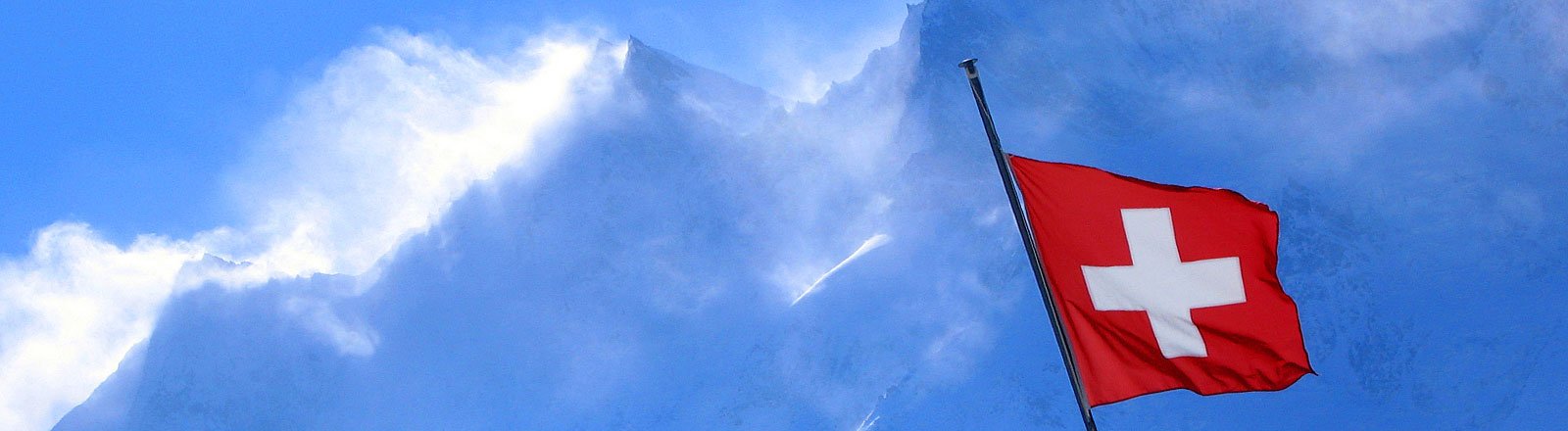 Schweizer Flagge vor Bergen und Wolken