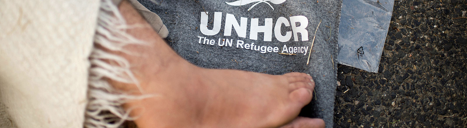 Fuß auf Decke mit UNHCR-Logo