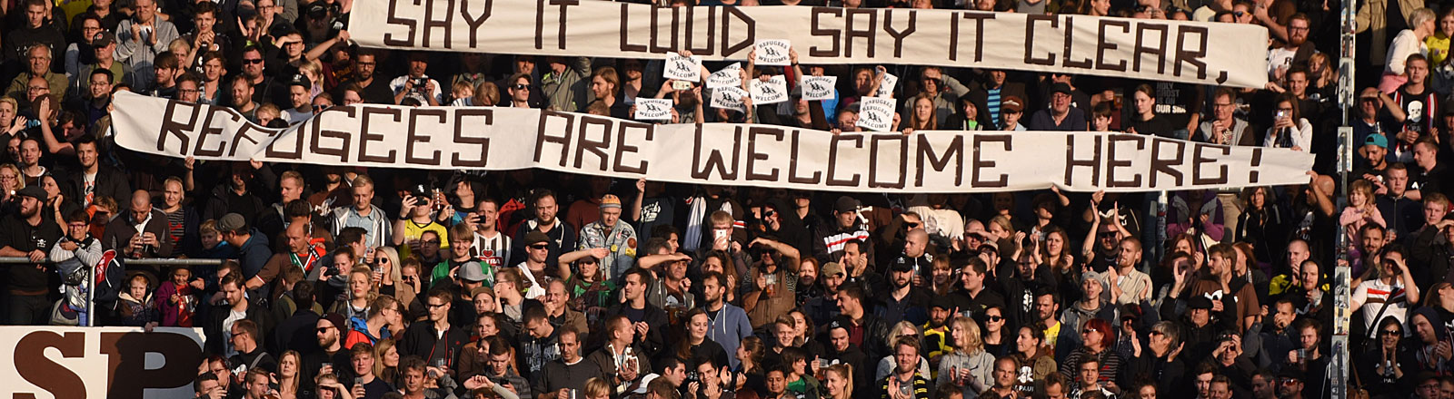 "Fans des FC St. Pauli mit  ""Refugees are welcome"" Poster im Stadion"