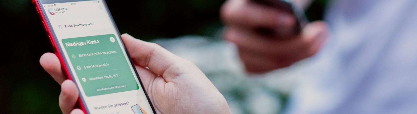 Zwei Menschen halten jeweils ein Smartphone mit der Corona-Warn-App in der Hand
