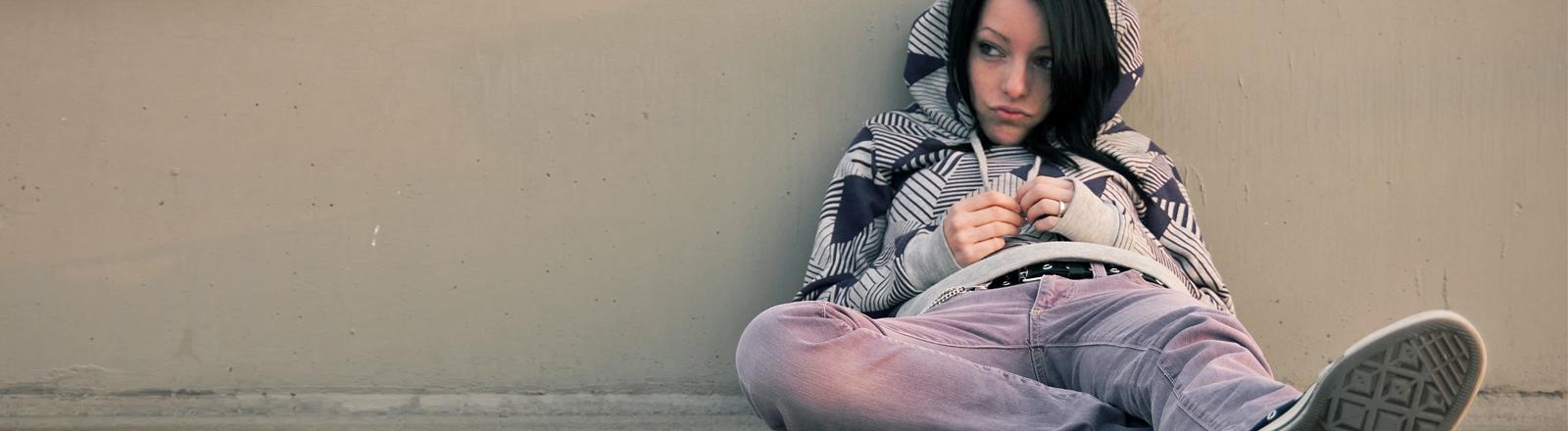 Eine Frau sitzt schmollend in der Ecke.