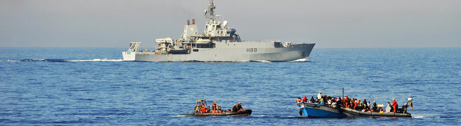 Flüchtlinge werden am 19.09.2015 im Mittelmeer von Bundeswehrsoldaten auf zwei Speedbooten von ihrem Holzboot abgeholt und anschließend zur Fregatte Schleswig-Holstein gebracht.