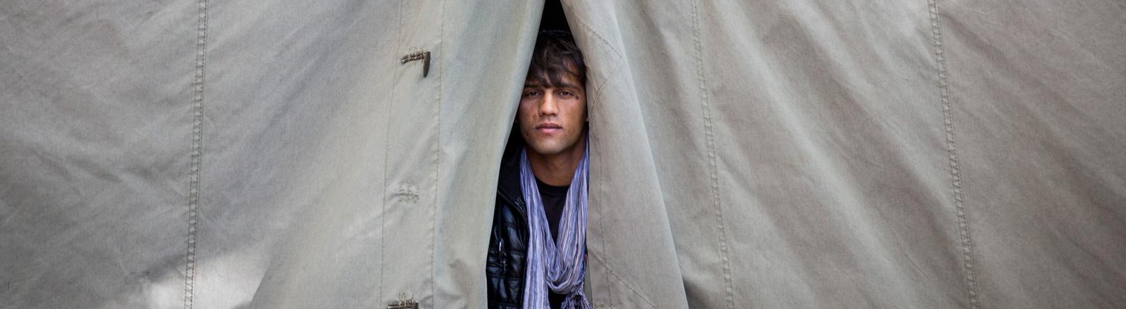 Ein Flüchtling schaut am 12.10.2015 bei Temperaturen um den Gefrierpunkt in Berlin in der Kruppstraße aus einem beheizten Zelt.