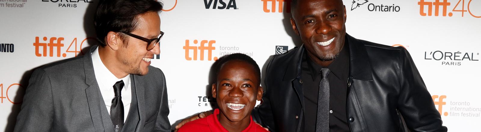 Beasts of No Nation Regisseur Cary Fukunaga (links) mit seinen beiden Hauptdarstellern Abraham Attah (Mitte) und Idris Elba am 13.09.2015.