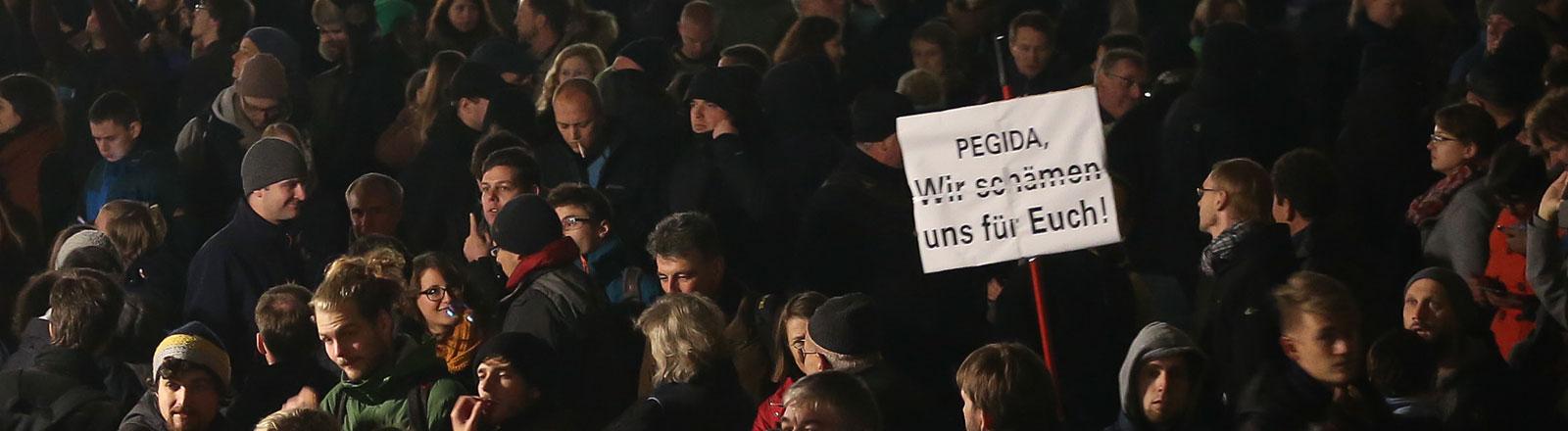 """Demonstranten tragen am 19.10.2015 in Dresden (Sachsen) ein Plakat mit der Aufschrift """"Pegida, Wir schämen uns für Euch""""."""