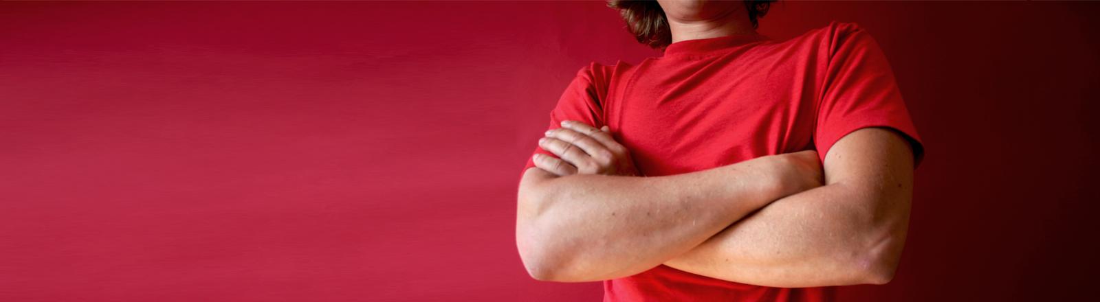Ein Mann im roten Shirt verschränkt die Arme vor der Brust.