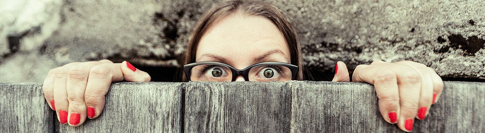 Junge Frau hinter einer Mauer