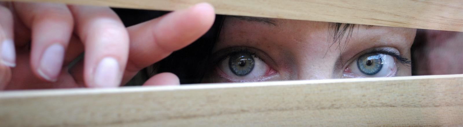Eine Frau schaut verstohlen durch die Jalousien.
