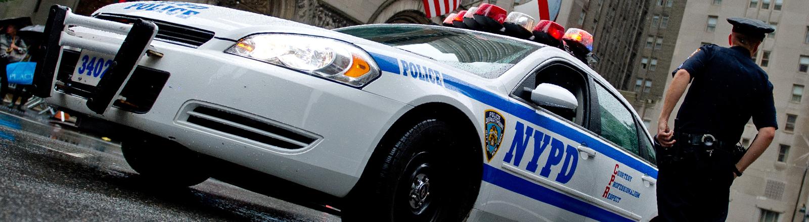 Ein Cop der New Yorker Polizei steht neben seinem Polizeiauto.
