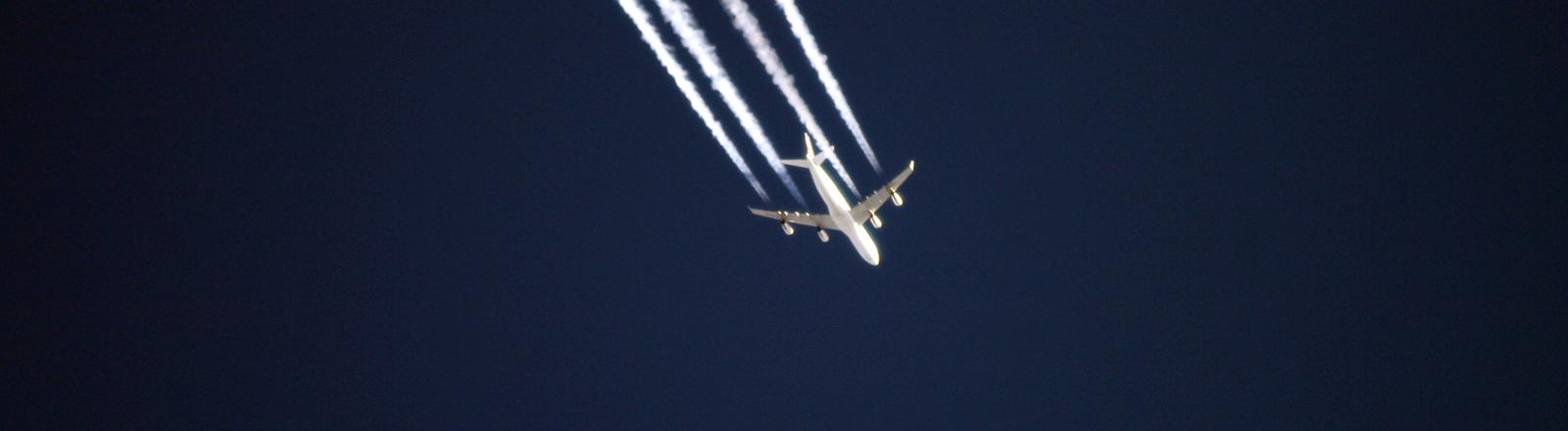 Flugzeug mit Kondenzstreifen am dunkelblauen Himmel