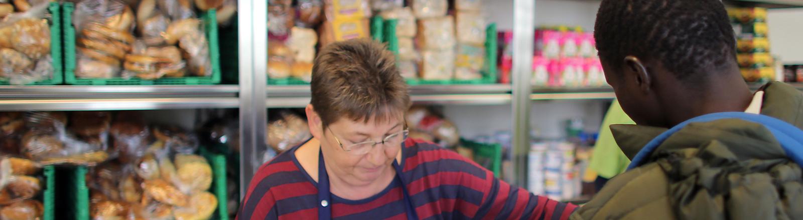 Mitarbeiter der Tafel geben am 30.10.2015 in Mechernich (Nordrhein-Westfalen) Lebensmittel an Flüchtlinge aus. An den Tafeln in Deutschland wird der Ton durch den Flüchtlingsandrang schärfer.