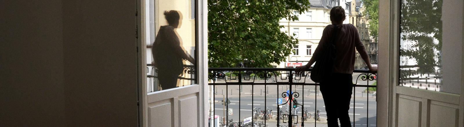 Frau steht am offenen Fenster einer leeren Wohnung