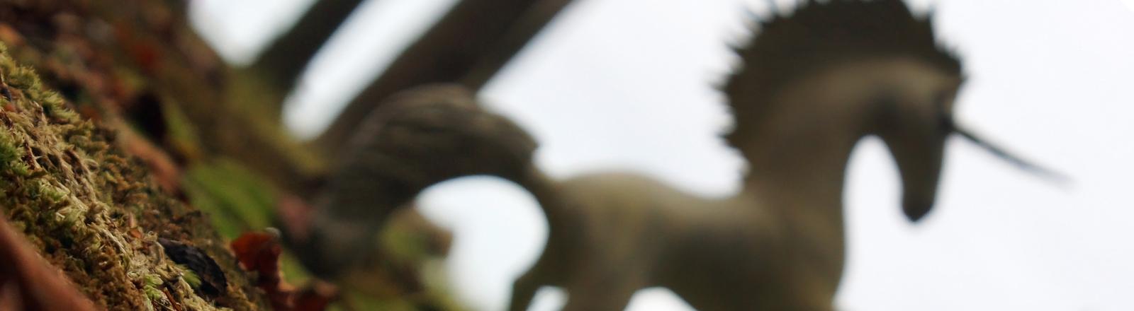 Ein recht unscharf fotografiertes Einhorn bäumt sich vor einem Menschen auf.