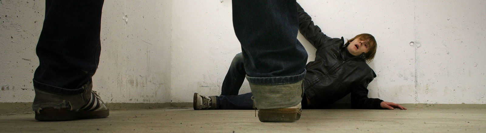 Mann kauert am Boden, im Vordergrund Beine eines anderen Mannes
