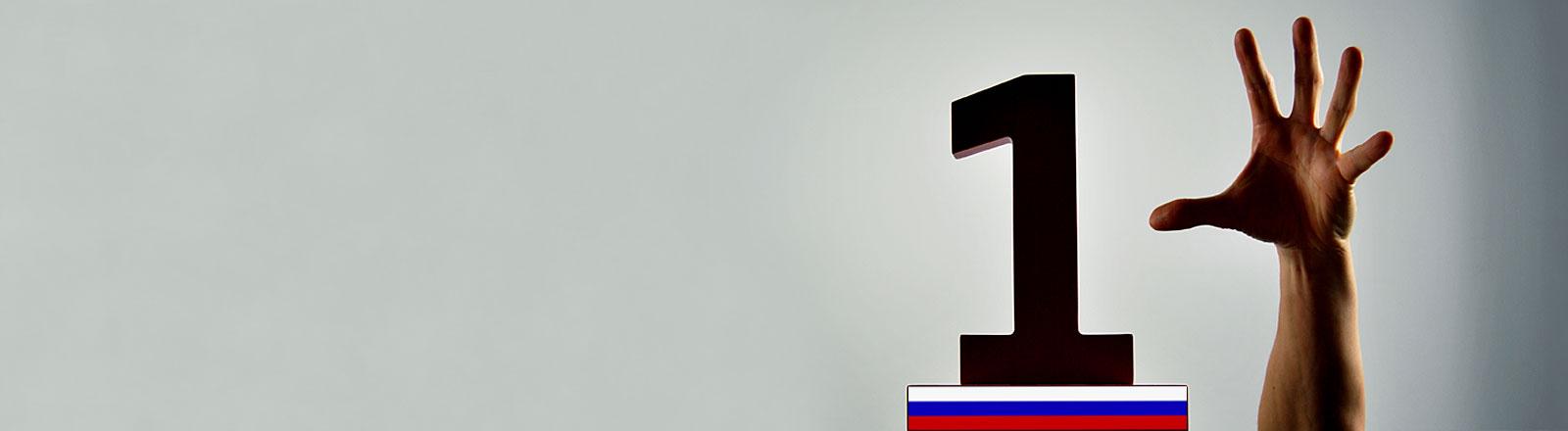 Hand greift nach Pokal mit der Ziffer 1 mit Russlandflagge