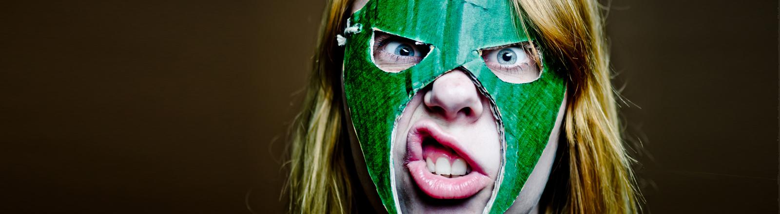 Eine Frau trägt eine Maske sieht aus wie eine Superheldin oder eine Wrestlerin.