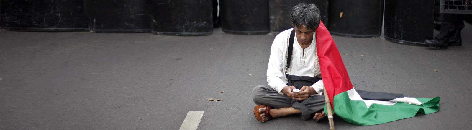 Ein Mann mit Palästinenserflagge sitzt auf dem Boden und schaut auf sein Handy.