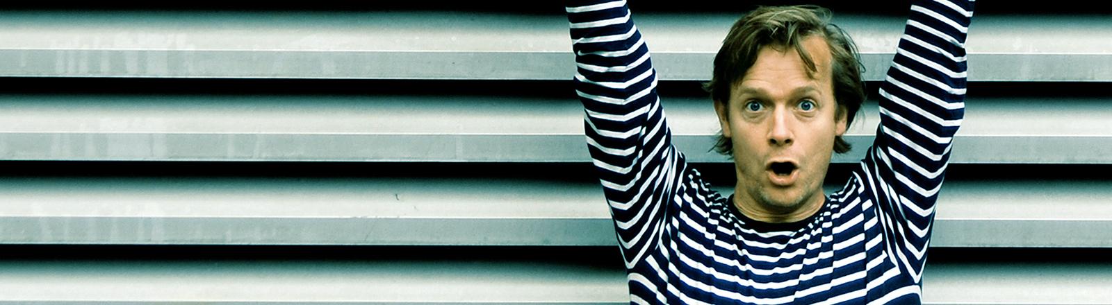 Ein Mann im gestreiften Pulli reißt vor einer gestreiften Wand die Hände hoch.